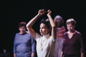 Kobieta w białej bluzce podnosi do góry obie ręce; w tle osoby się jej przyglądają