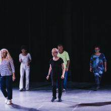 Grupa ośmiu starszych osób w tańcu w sali teatralnej