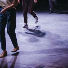 Nogi kilku osób na posadzce sali teatralnej