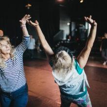 Dwie kobiety z wyciągniętymi do góry rękami
