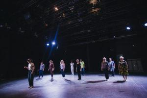 Grupa osób tańczy w sali teatralnej