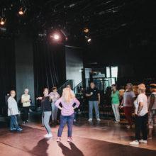 Grupa osób stoi w półokręgu w sali teatralnej. Dwie osoby tańczą pośrodku.