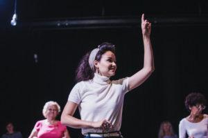 Kobieta w białej bluzce podnosi rękę do góry, w tle dwie starsze kobiety]