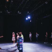Osoby stoją w dwóch rzędach, przed nimi kobieta w białej bluzce