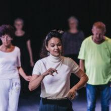 Kobieta w białej bluzce tańczy z uczestnikami warsztatów
