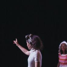 Kobieta w białej bluzce pokazuje palcem przed siebie