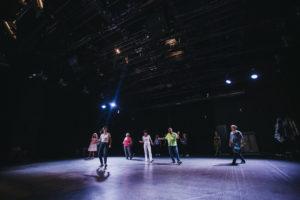 Uczestnicy warsztatów tańczą na scenie sali teatralnej