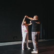 Starsza kobieta i mężczyzna tańczą. W tle czarna kotara