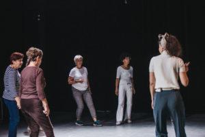 Pięć kobiet stojących luźno w sali teatralnej