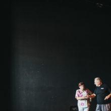 Starsza kobieta i mężczyzna rozmawiają. W tle czarna kotara