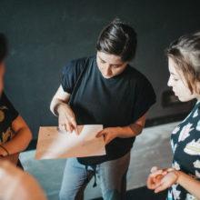 Kobieta pokazuje palcem na kartkę. Kilka osób przygląda się.