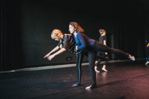 Dwie kobiety pochylają się do przodu wyciągając nogę dla przeciwwagi