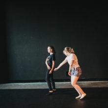 Dwie kobiety podczas tańca; jedna z nich wyciąga rękę do drugiej