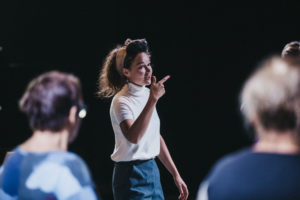 Kobieta w białej koszulce i opasce na włosach pokazuje coś ręką