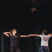 [Dwie kobiety stoją w wyprostowanej pozie, trzymając się wzajemnie za wyciągnięte przedramiona