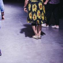 Osoba w sukience w kwiaty i w srebrnych butach stoi w sali teatralnej