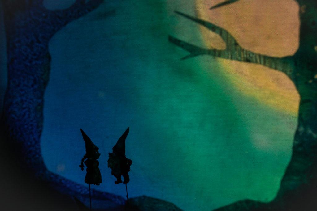 Na niebiesko-zielonym tle widać dwa czarne cienie skrzatów. Po bokach widać cienie drzew.