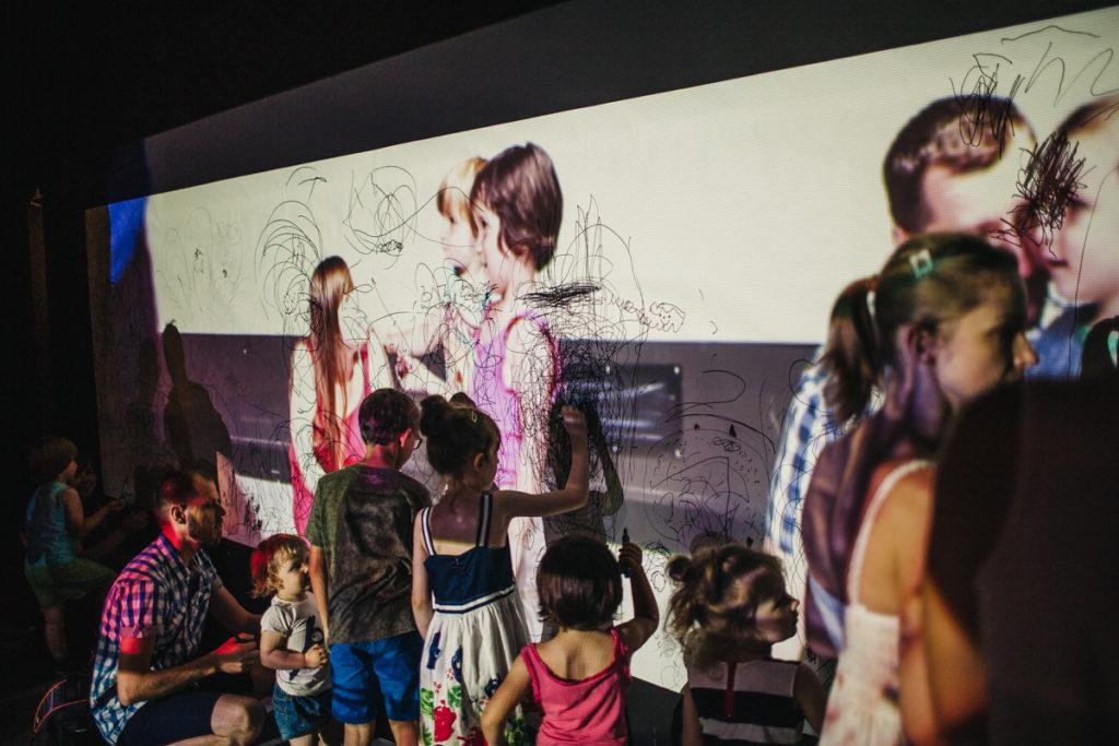 AD [Na zdjęciu grupa dzieci i dorosłych rysuje po białym papierze rozpiętym na ścianie. Na papier rzucony jest obraz projekcji wideo.]