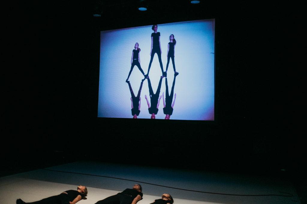 AD [Na zdjęciu ekran, na którym widać grupę dzieci – trójka jest w rozkroku, stopami styka się z drugą trójką. Pod ekranem na białej podłodze leżą dzieci w czarnych strojach.]