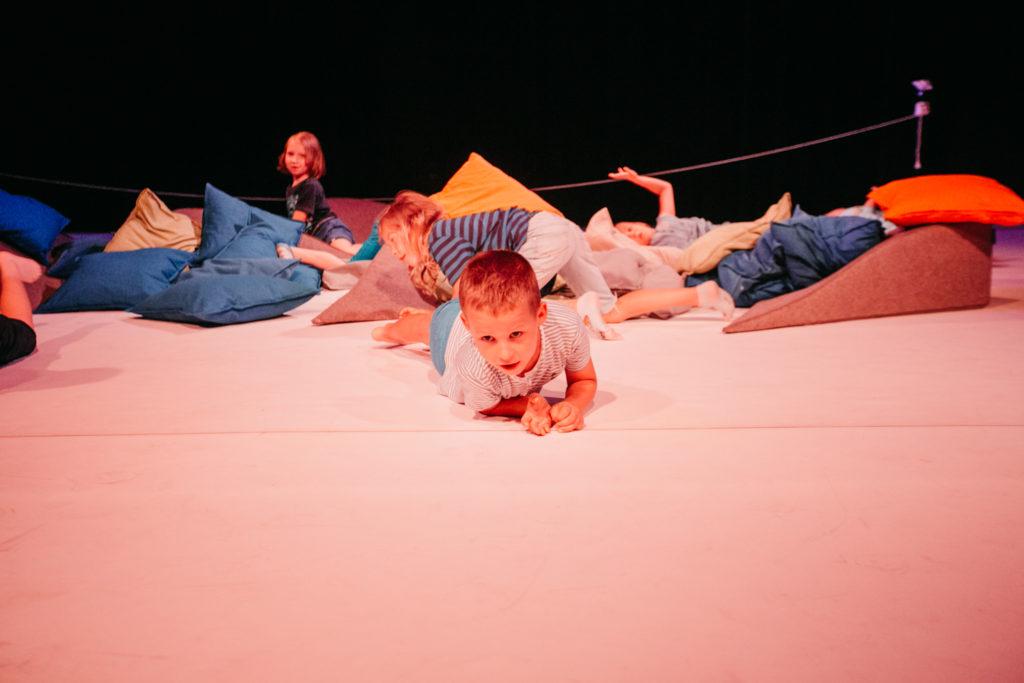AD [Na zdjęciu biała podłoga, na której leży stos kolorowych poduszek. Na poduszkach turlają się dzieci.]