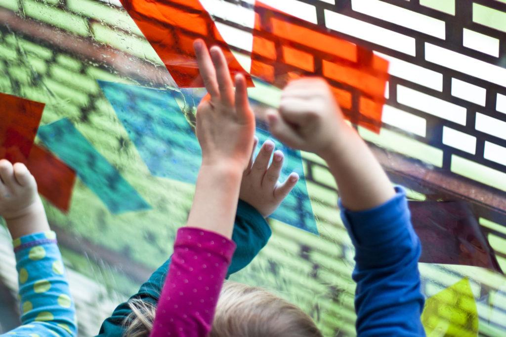 [Kolorowe zdjęcie. Na zdjęciu widać ręce dzieci, które trzymają różnokolorowe szkiełka.]