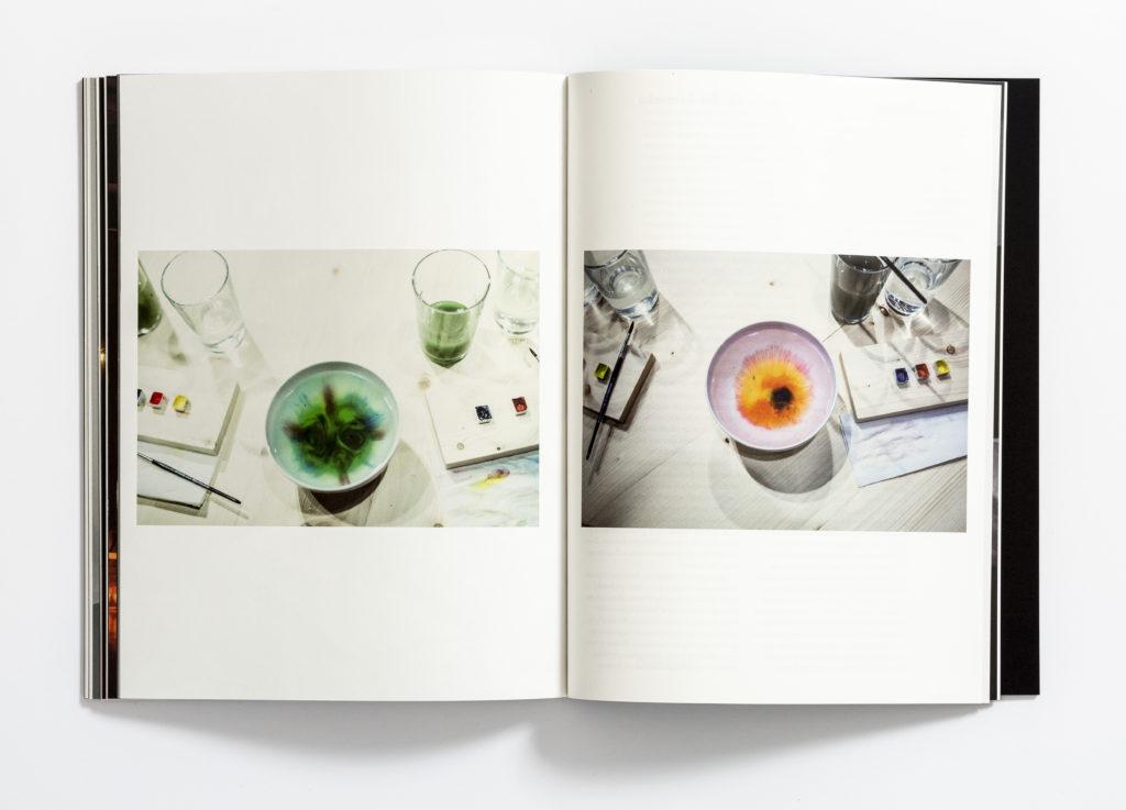 """[Zdjęcie dwóch stron książki """"Zapraszanie. Sarkis-Kantor"""". Na zdjęciu widać miseczki i szklanki z wodą, kolorowe farbki oraz pędzelki.]"""