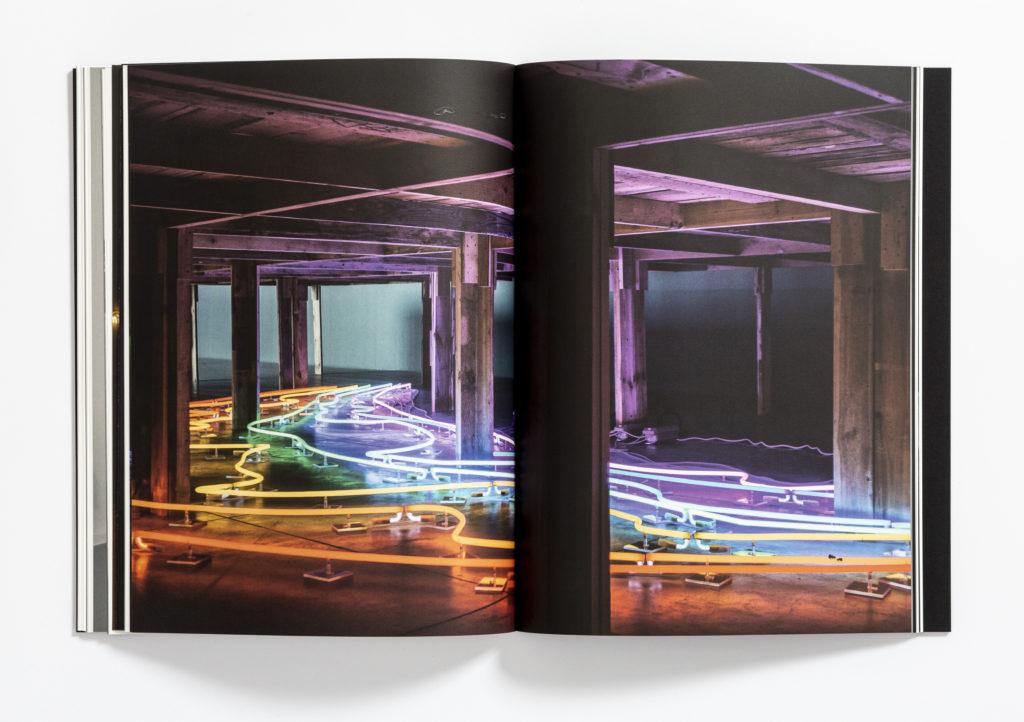 """[Kolorowe zdjęcie książki """"Zapraszanie. Sarkis-Kantor"""". Zdjęcie przedstawia drewniany stół, pod nim neon. Neon składa się z kolorowych linii.]"""