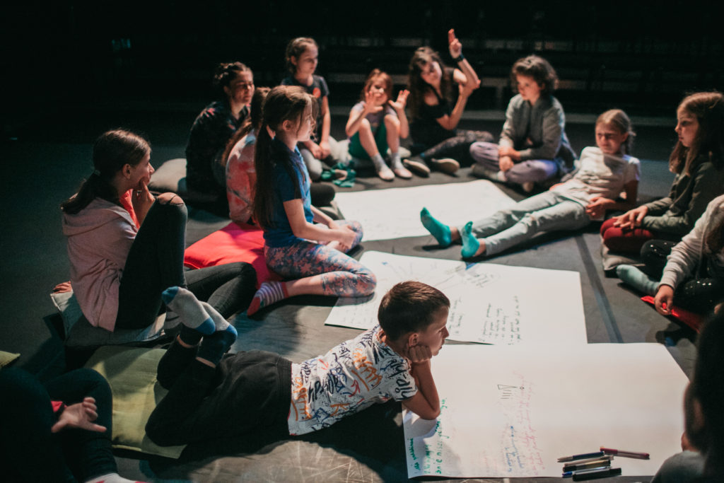 [Na zdjęciu grupka dzieci siedzi lub leży na podłodze wokół dużych białych kartek. Dzieci rozmawiają ze sobą.]