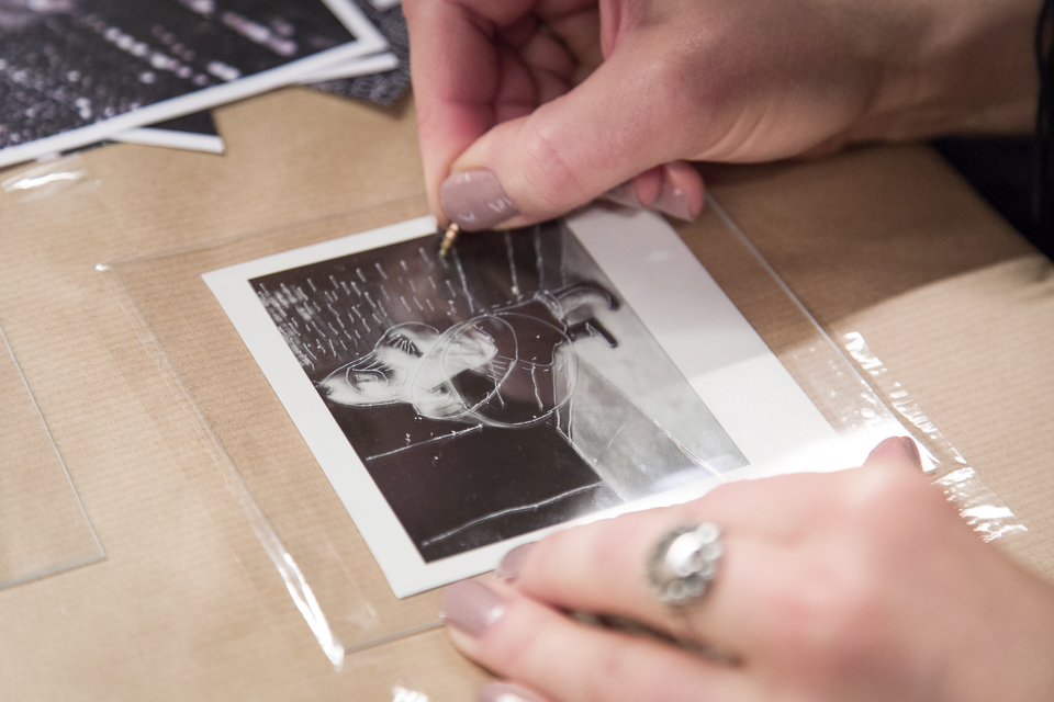 Na zdjęciu widać dłonie kobiety, która ostrym narzędziem drapie czarno-białą fotografię.]