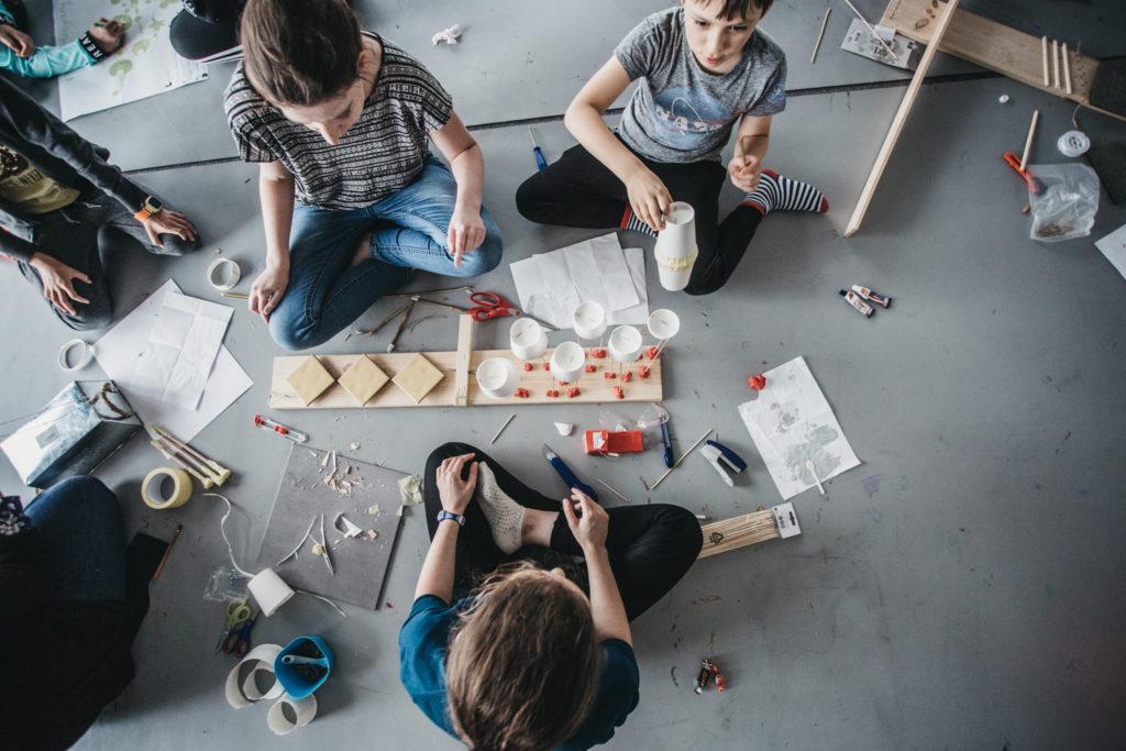 Zdjęcie przedstawia trójkę chłopców siedzących na podłodze pośród różnych przedmiotów: kubków, pędzelków, taśm klejących.