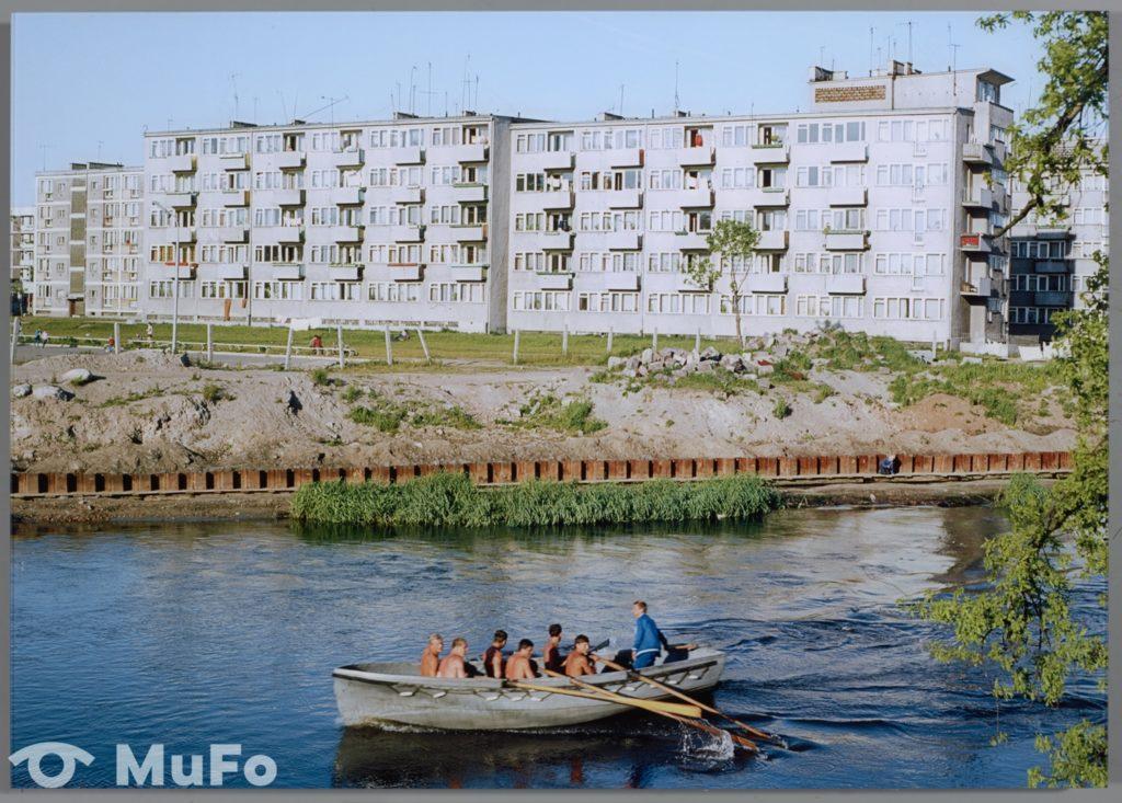 Kolorowe zdjęcie, które przedstawia bloki i rzekę. Płyną po niej w łódce mężczyźni.