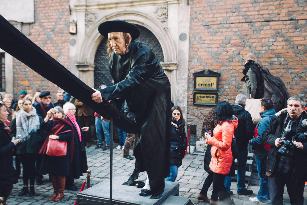 Na zdjęciu grupa ludzi na ulicy, wśród nich aktor przebrany za chasyda, który trzyma czarną deskę.