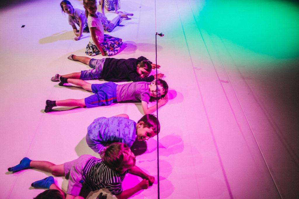 Na podłodze w kolorowym świetle leżą dzieci, dziewczynki i chłopcy. Nad nimi wisi linka, pod którą próbują się przeczołgać.