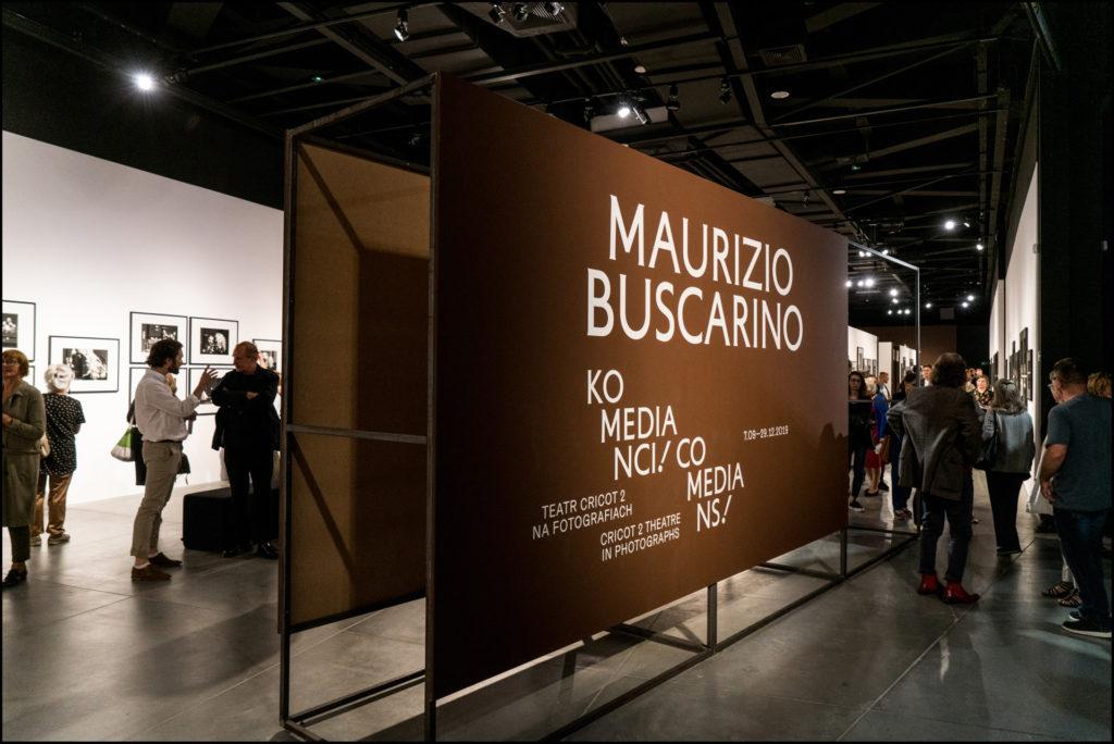 """Zdjęcie przedstawia ujęcie z wernisażu wystawy fotografii """"Maurizio Buscarino. Komedianci!"""". Na zdjęciu widać kobiety i mężczyzn oglądających wystawę. Na środku sali ustawiony jest brązowy baner z białymi napisami """"Maurizio Buscarino. Komedianci!""""."""