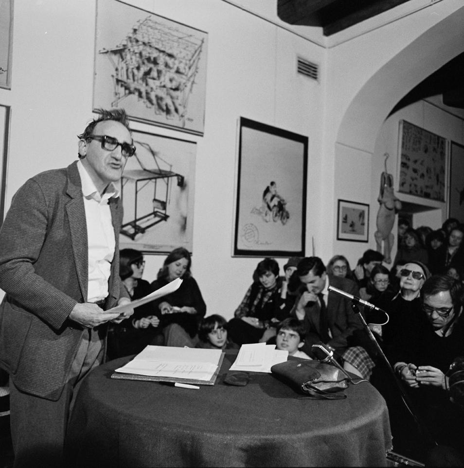 [Czarno-białe zdjęcie. Widać na nim przemawiającego Tadeusza Kantora oraz publiczność podczas otwarcia Ośrodka Teatru Cricot 2 w 1980 roku.]