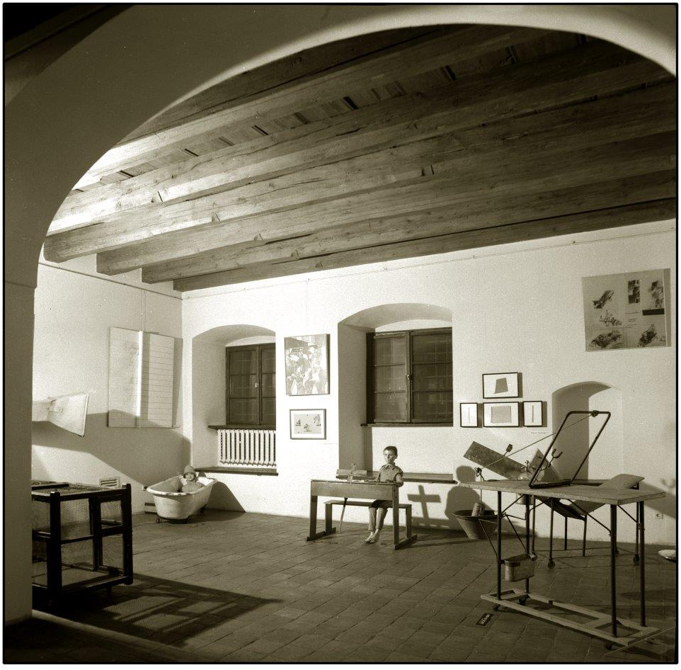 [Zdjęcie w kolorze sepii przedstawiające wnętrze Ośrodka Teatru Cricot 2 z 1980 roku. Na zdjęciu widać okna oraz obiekty ze spektakli Tadeusza Kantora.]