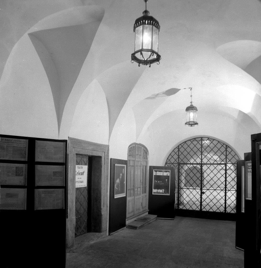 [Czarno-białe zdjęcie przedstawiające wnętrze Ośrodka Teatru Cricot 2 w 1980 roku. Widać na nim korytarz, drewniane drzwi, plakaty Teatru Cricot 2. Na końcu korytarza znajduje się żelazna brama.]