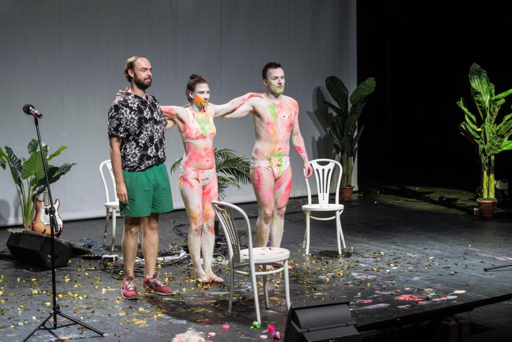 [Kolorowe zdjęcie, na którym widać trójkę aktorów – kobietę i dwóch mężczyzn. Wszyscy trzymają się za ramiona, stojąc do ukłonu przed widownią.]