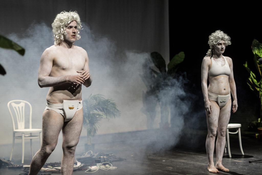 [Kolorowe zdjęcie, które przedstawia dwójkę aktorów - kobietę i mężczyznę. Aktorzy mają na sobie bieliznę, a na głowach peruki.]