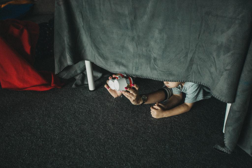 [Kolorowe zdjęcie, na którym widać dziecko i kobietę pod stołem, który przykrywa koc.]