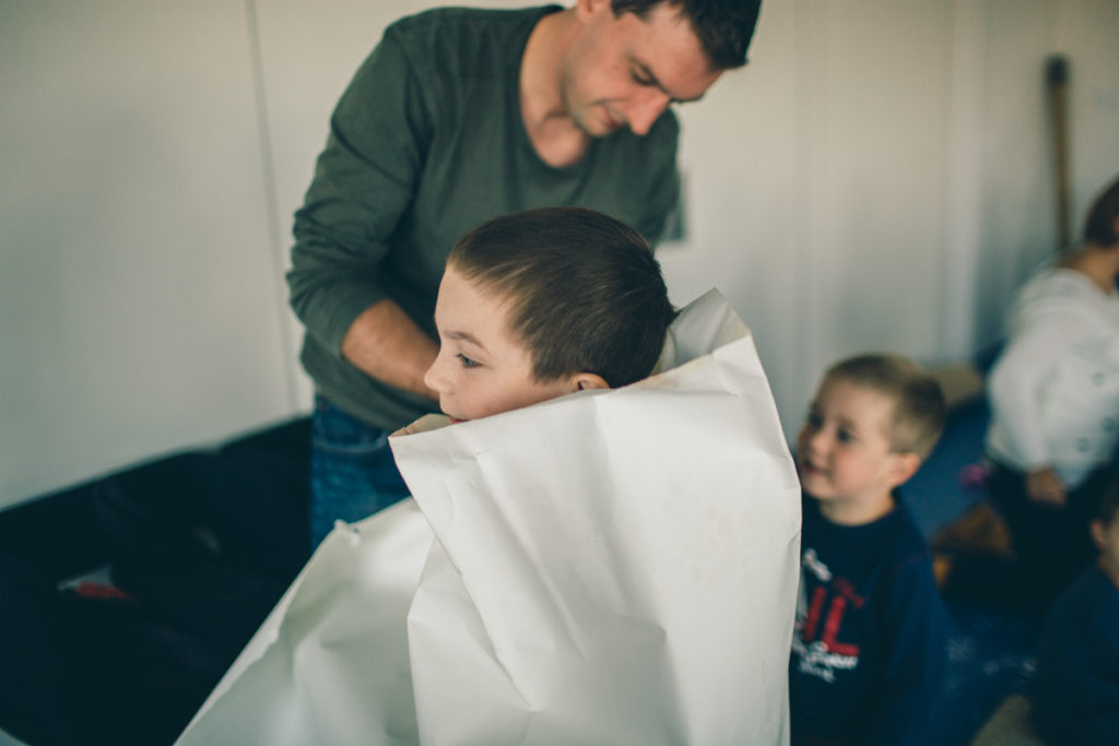 [Kolorowe zdjęcie, na którym widać chłopca owiniętego w papier przez prowadzącego warsztaty.]