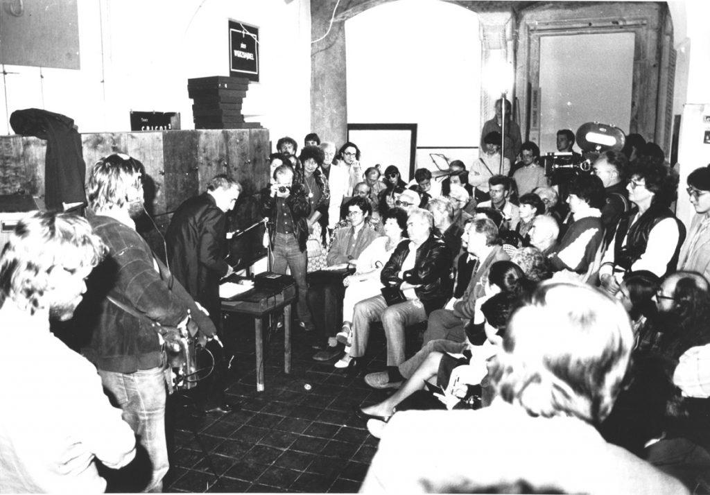 [czarno-białe zdjęcie, przedstawiające Kantora oraz tłum dziennikarzy w pomieszczeniu na Kanoniczej.]