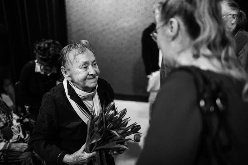 [AD:czarno-białe zdjęcie przedstawiające Marię Stangret z bukietem tulipanów.]