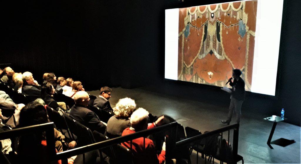 [AD: zdjęcie przedstawia widownię oglądającą projekcję w przyciemnionej sali. Przed widzami stoi prelegentka.]