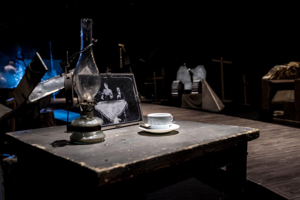 [AD: na zdjęciu cześć ekspozycji stałej: stolik z lampanaftową, zdjęciem w ramce i filiżanką.