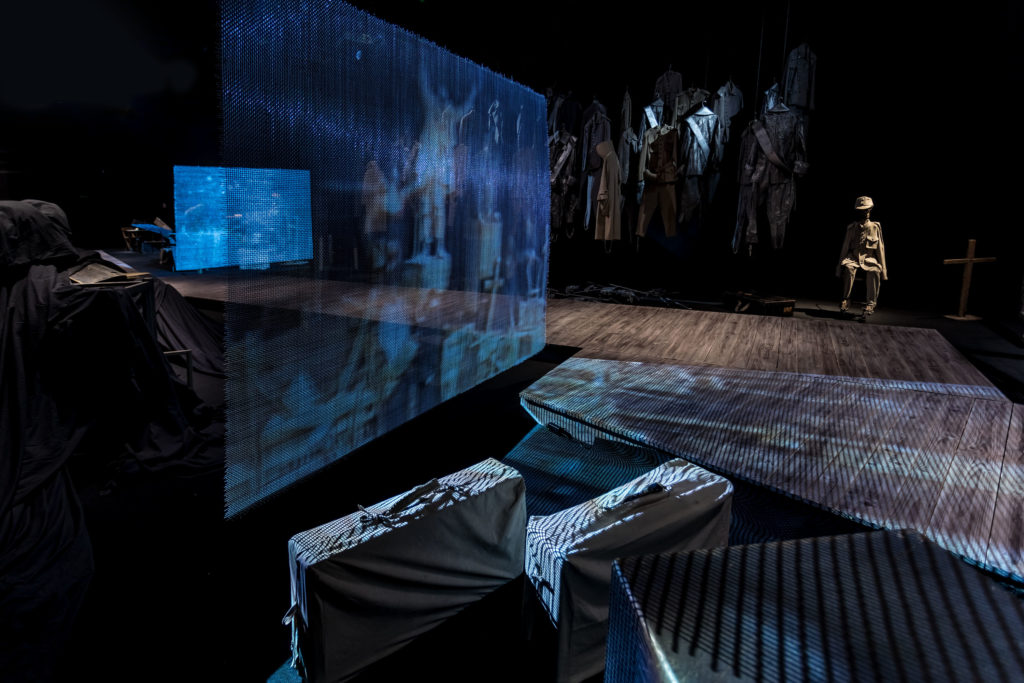 [AD: Na zdjęciu fragment rampy dla zwiedzających oraz cześć ekspozycji stałej: niebieski ekran z projekcją, na pierwszym planie walizki.