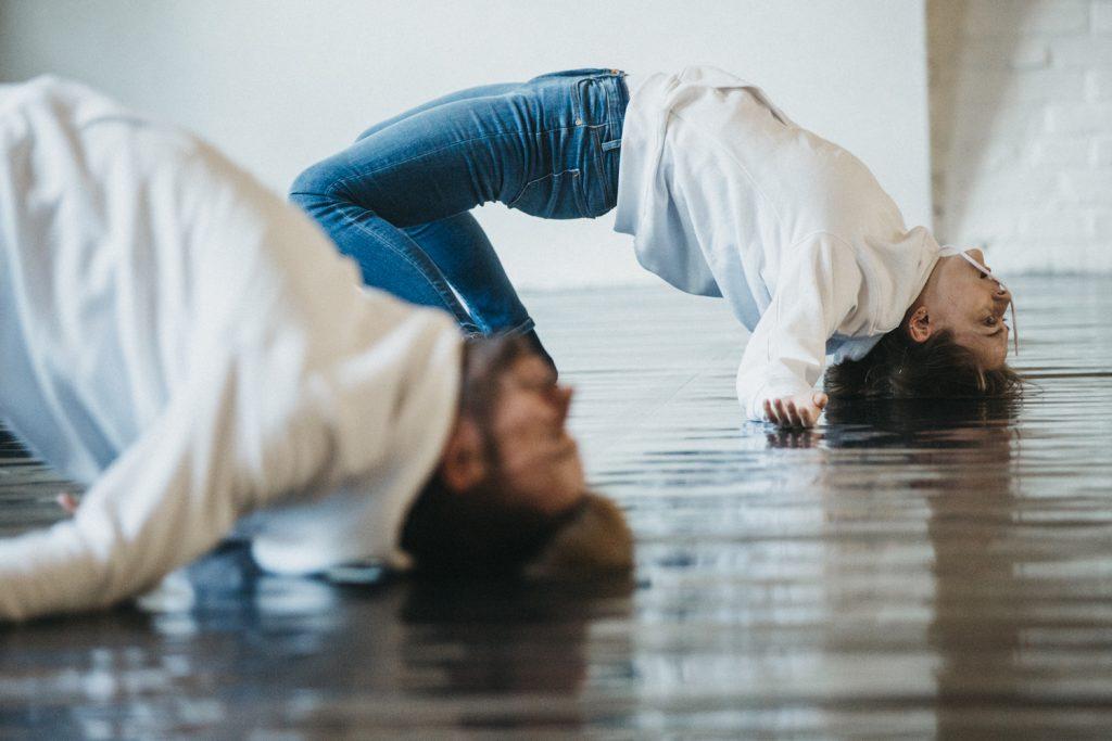 [AD: Na zdjęciu dójka tancerzy wygięta w mostku, opierająca się głowami o podłogę.]