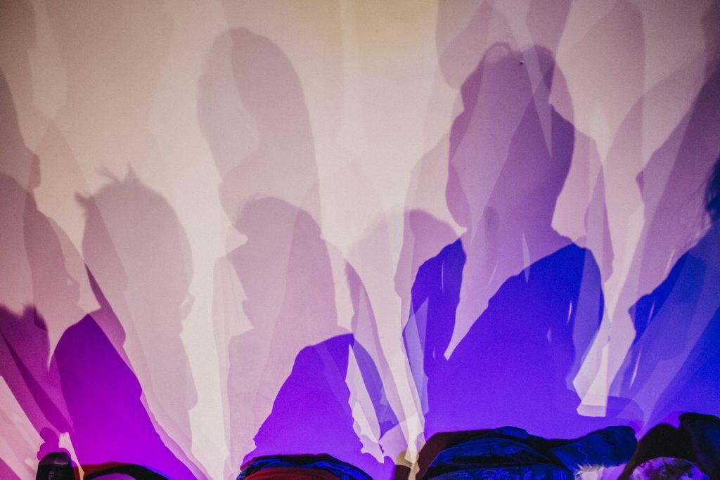 Kolorowe zdjęcie: na ścianie odbijają się cienie dzieci, oświetlone na fioletowo.