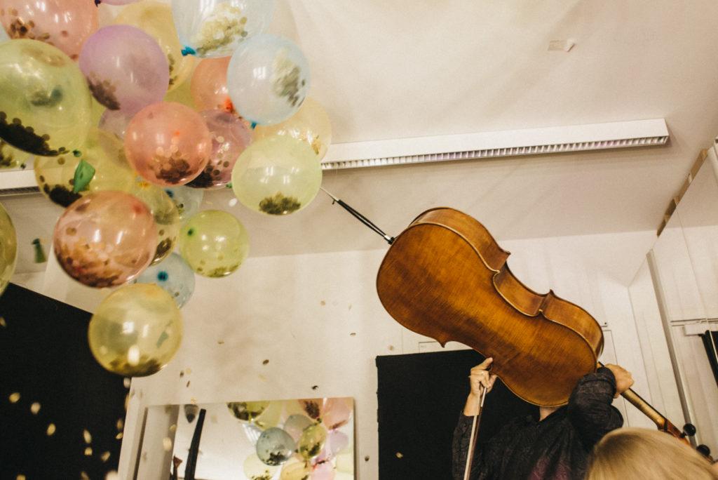 """Kolorowe zdjęcie z koncertu w ramach """"Polifonii dzieciom"""". W lewym górnym rogu widać różnokolorowe zdjęcia, w prawym dolnym męskie ręce trzymające wiolonczelę."""