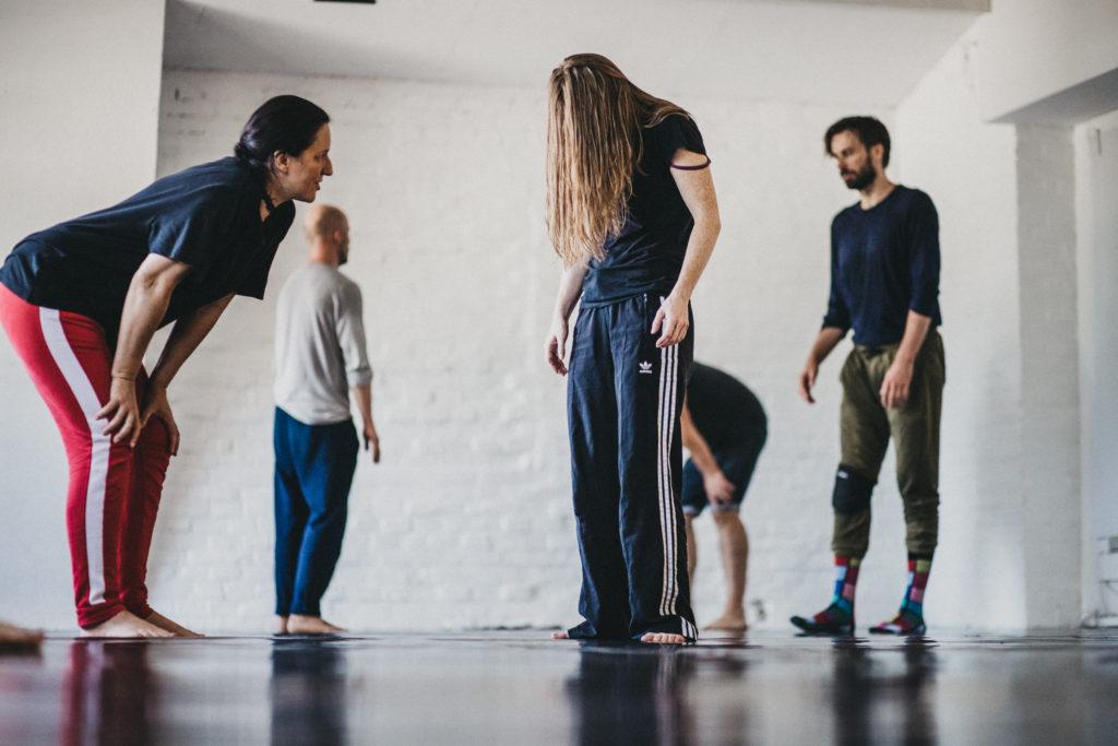 """Kadr do spektaklu """"Kantor. Burza"""". Na zdjęciu tancerze wraz z choreografką Anną Godowską."""